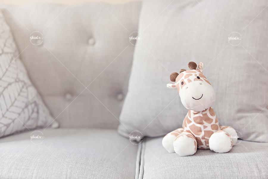 stuffed giraffe on a gray sofa