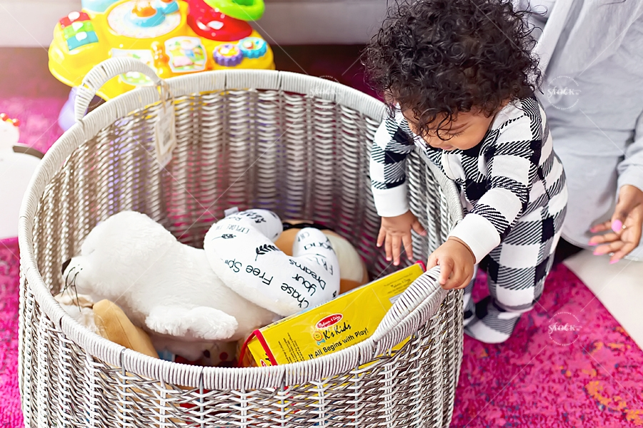 baby reaching into a basket full of toys