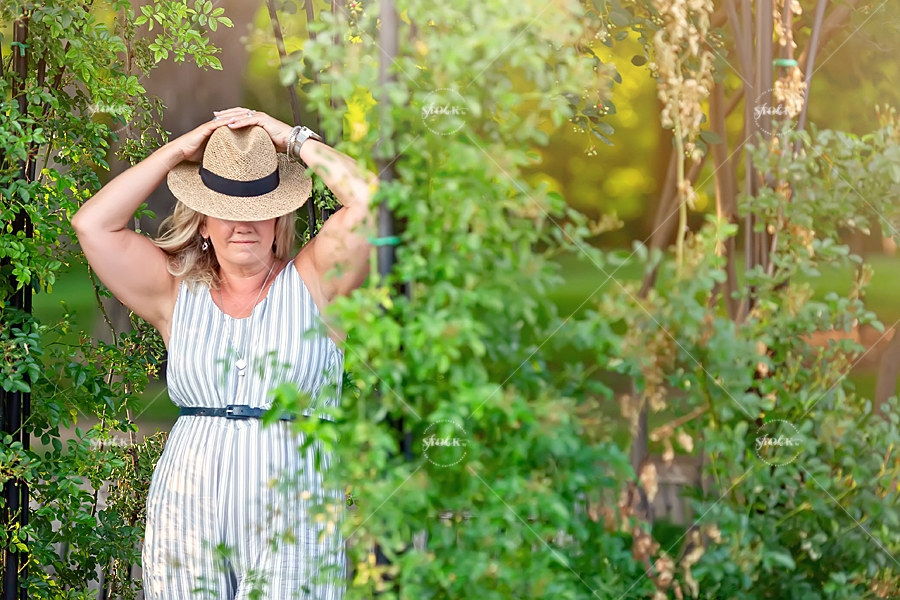 middle aged woman wearing a hat in Ottawa rose garden